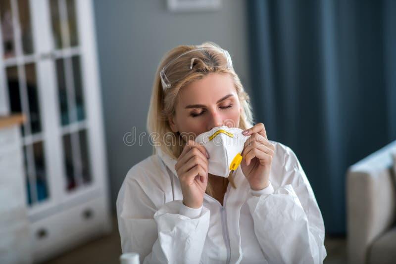 Ξανθιά γυναίκα με λευκά ρούχα εργασίας που φοράει αναπνευστική στοκ εικόνα