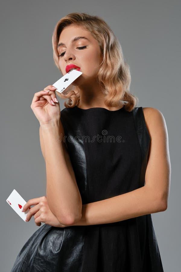 Ξανθιά κοπέλα με μαύρο κομψό φόρεμα που δείχνει δυο τραπουλόχαρτα, ποζάρει σε γκρίζο φόντο Ψυχαγωγία τυχερών παιχνιδιών στοκ εικόνες