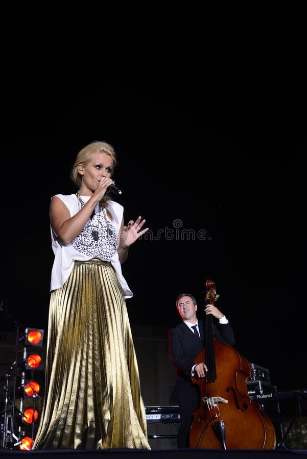 Ξανθός θηλυκός τραγουδιστής στη σκηνή, μουσικός στο υπόβαθρο στοκ εικόνες