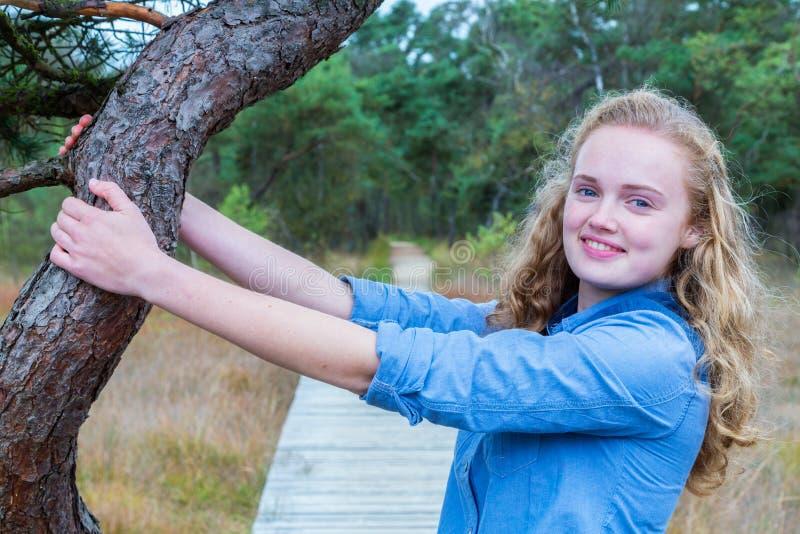 Ξανθός κορμός δέντρων εκμετάλλευσης κοριτσιών στη φύση στοκ φωτογραφίες
