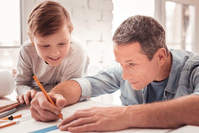 Ξανθός-μαλλιαρός γιος που προσέχει τους αριθμούς σχεδίων πατέρων του για την κατηγορία γεωμετρίας στοκ εικόνες με δικαίωμα ελεύθερης χρήσης