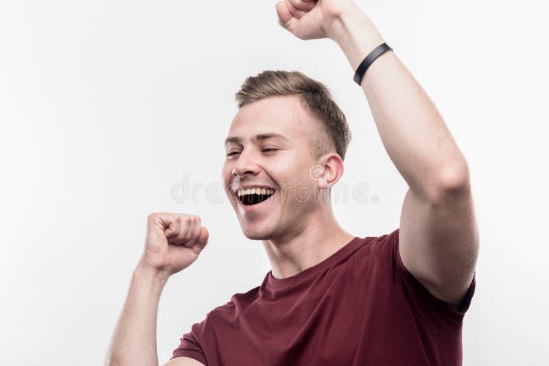 Ξανθός-μαλλιαρός σπουδαστής που αισθάνεται πολύ αστείος και ευτυχής μετά από να περάσει το διαγωνισμό στοκ φωτογραφία