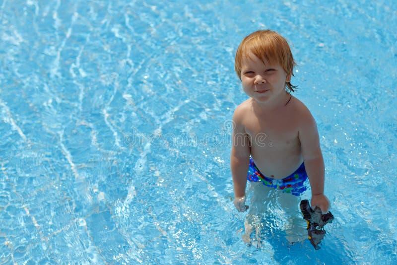 Ξανθός-μαλλιαρό μικρό παιδί που στέκεται στην πισίνα στοκ φωτογραφία