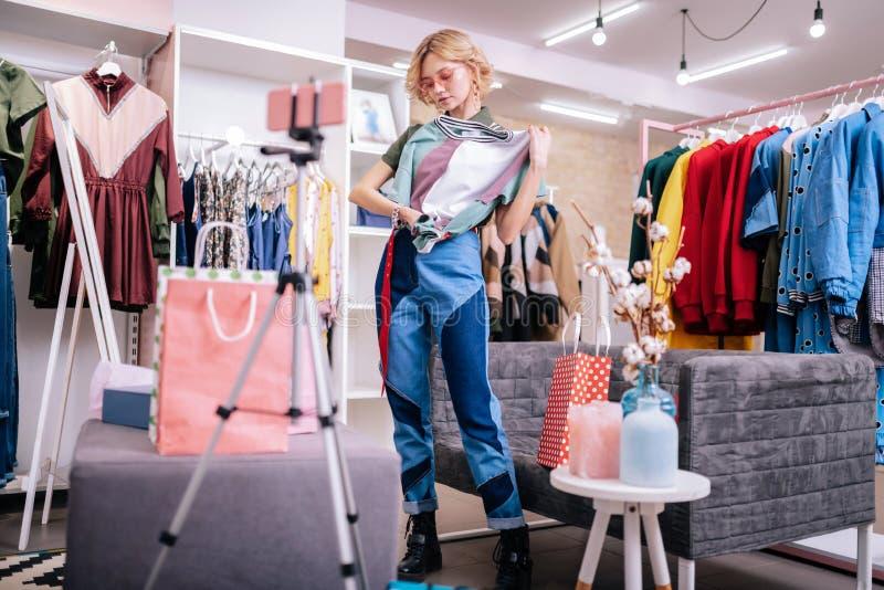 Ξανθός shopaholic λέγοντας τα μυστικά μόδας της ενώ μαγνητοσκόπηση blog στοκ εικόνες