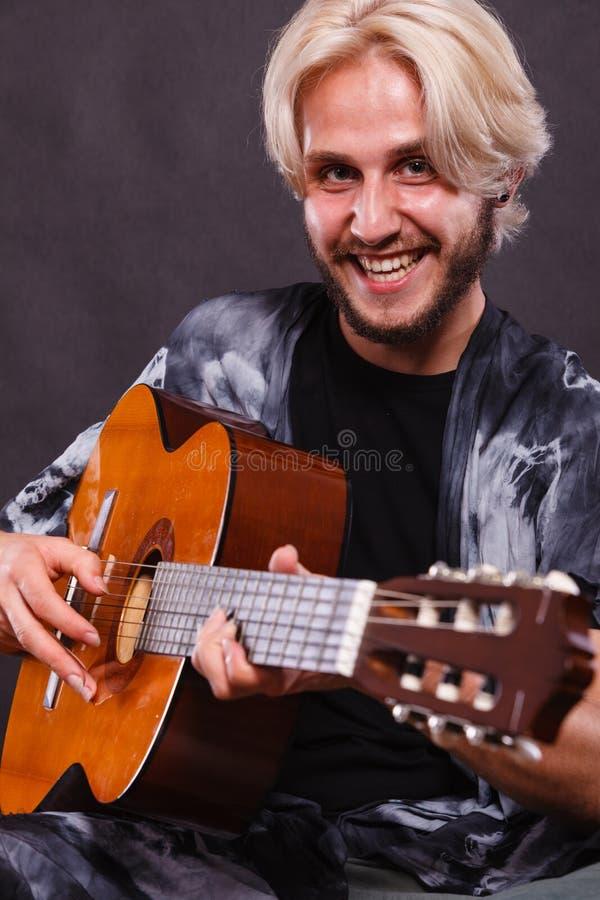 Ξανθό άτομο που παίζει την ακουστική κιθάρα στοκ φωτογραφία