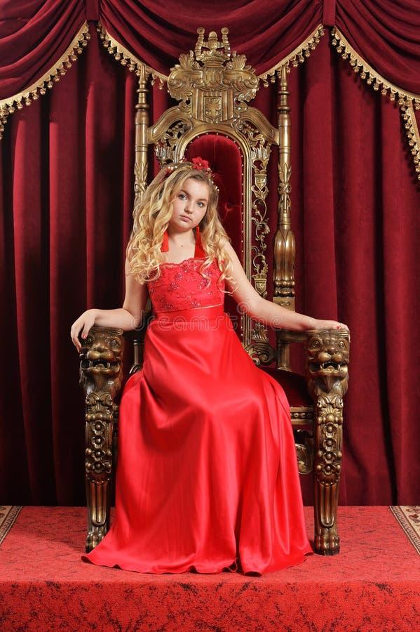 Ξανθό έφηβη στη φωτεινή κόκκινη συνεδρίαση φορεμάτων στην εκλεκτής ποιότητας καρέκλα στοκ φωτογραφίες με δικαίωμα ελεύθερης χρήσης