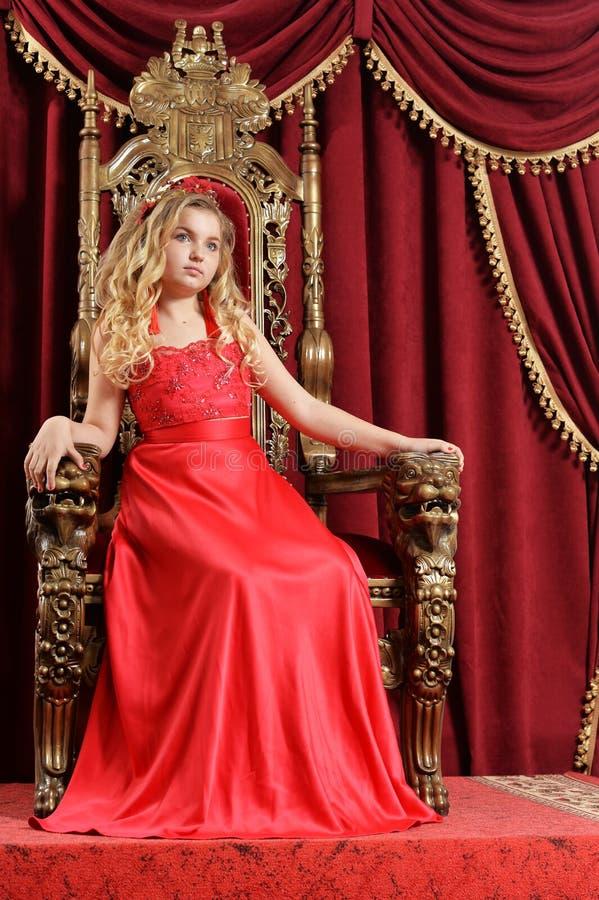Ξανθό έφηβη στη φωτεινή κόκκινη συνεδρίαση φορεμάτων στην εκλεκτής ποιότητας καρέκλα στοκ φωτογραφία με δικαίωμα ελεύθερης χρήσης