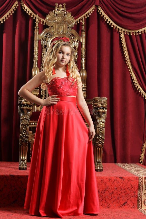 Ξανθό έφηβη στο φωτεινό κόκκινο φόρεμα που στέκεται μπροστά από το vin στοκ εικόνα