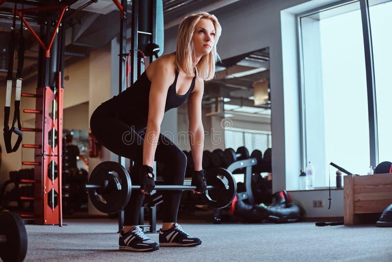 Ξανθό αθλητικό θηλυκό sportswear που κάνει deadlift με το barbell στη λέσχη ή τη γυμναστική ικανότητας στοκ εικόνες