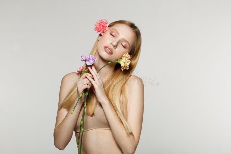 Ξανθό κορίτσι άνοιξη με τις ιδιαίτερες προσοχές που κρατά τα λουλούδια στα χέρια στοκ εικόνες
