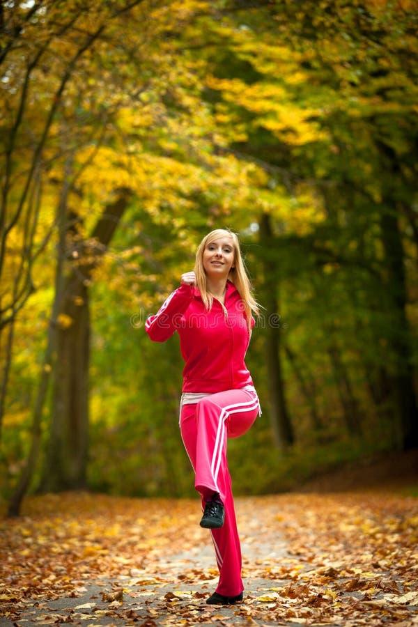 Ξανθό κορίτσι γυναικών ικανότητας κατάλληλο που κάνει την άσκηση στο φθινοπωρινό πάρκο αθλητισμός στοκ εικόνα με δικαίωμα ελεύθερης χρήσης