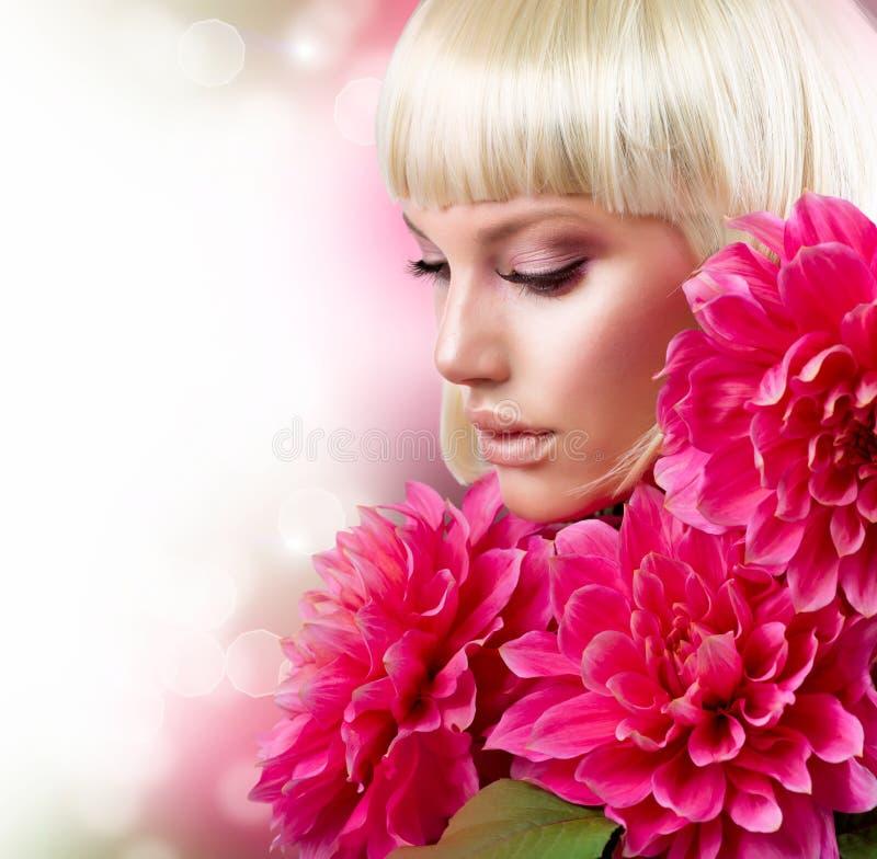 Ξανθό κορίτσι με τα λουλούδια στοκ εικόνα με δικαίωμα ελεύθερης χρήσης