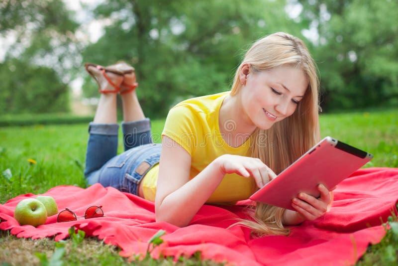 Ξανθό κορίτσι που βρίσκεται στο πάρκο με την ταμπλέτα στο κόκκινο coverlet στοκ φωτογραφίες με δικαίωμα ελεύθερης χρήσης