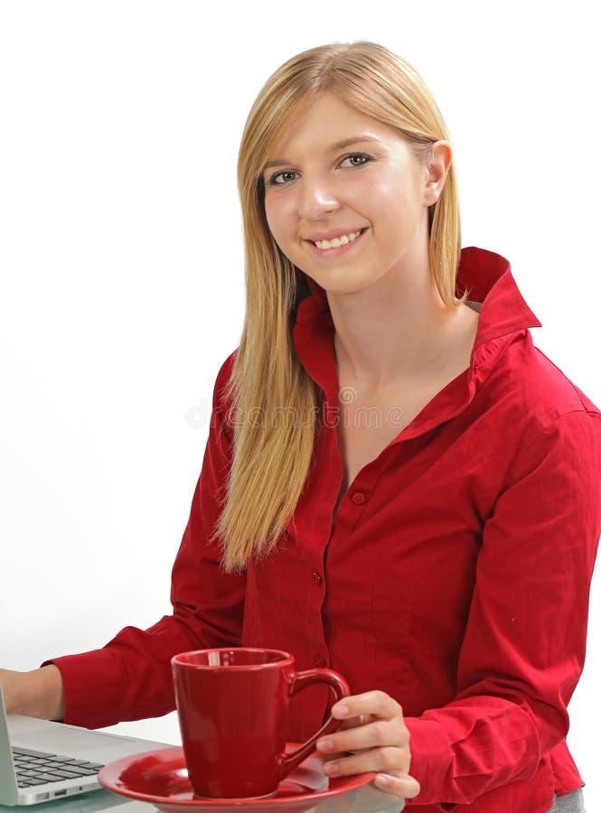 Ξανθό κορίτσι που εργάζεται σε έναν υπολογιστή με τον καφέ στοκ εικόνες