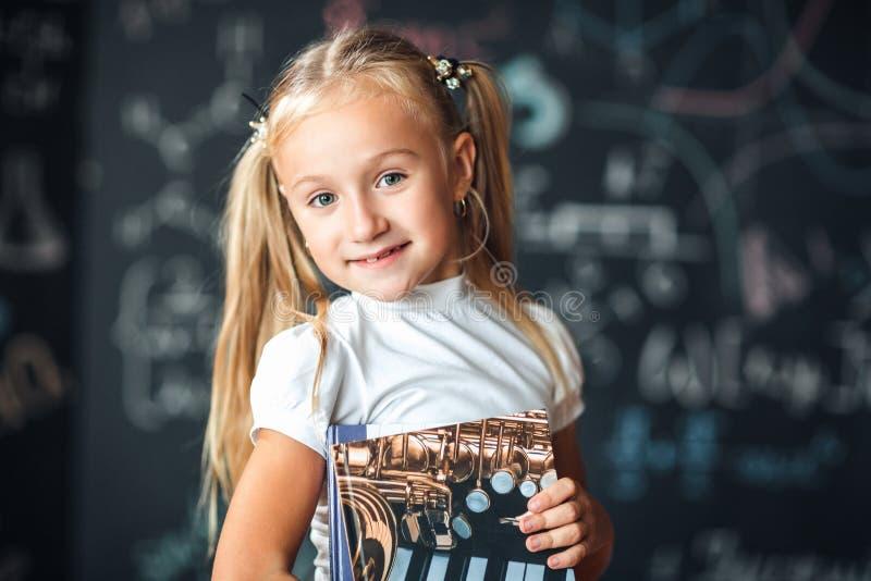 Ξανθό κορίτσι που στέκεται κοντά σε μια μαύρη πλάκα με έναν σωρό των βιβλίων o   Σχολική έννοια στοκ εικόνα