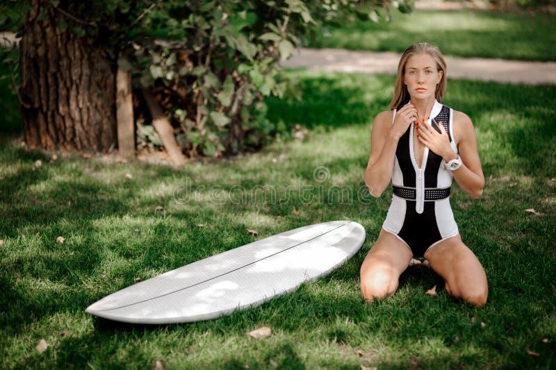 Ξανθό κορίτσι που στέκεται στα γόνατά της κοντά στο wakeboard στοκ εικόνες