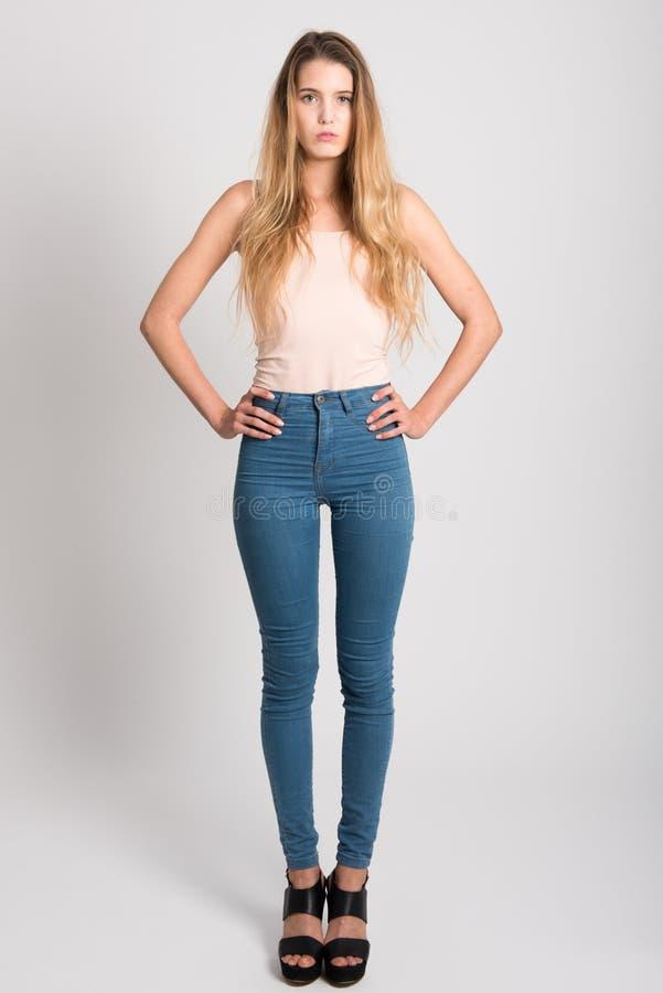 Ξανθό κορίτσι που φορά το τζιν παντελόνι και την μπλούζα όμορφες νεολαίες γυναικών στούντιο ζευγών χορεύοντας καλυμμένες στοκ εικόνα