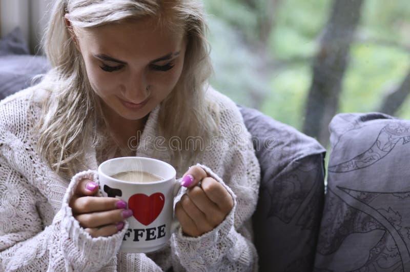 Ξανθό κορίτσι σε ένα θερμό πουλόβερ με μια συνεδρίαση φλιτζανιών του καφέ στο α στοκ φωτογραφίες