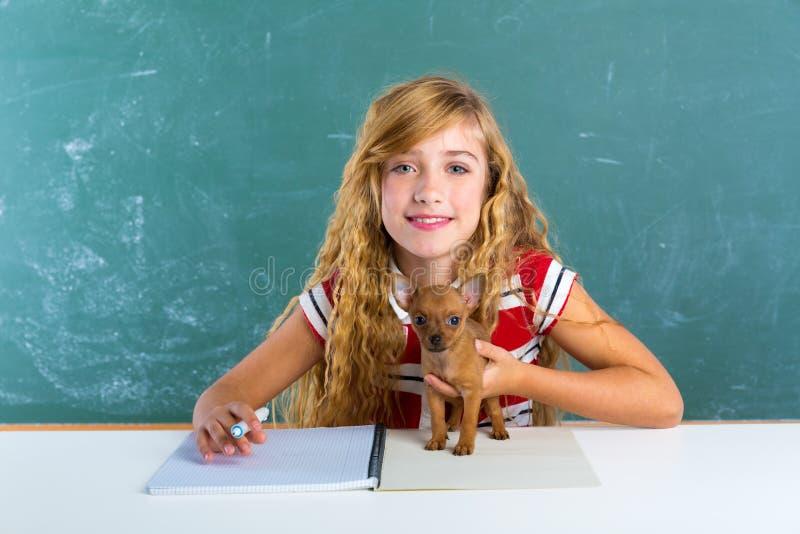 Ξανθό κορίτσι σπουδαστών με το σκυλί κουταβιών στον πίνακα κατηγορίας στοκ εικόνες
