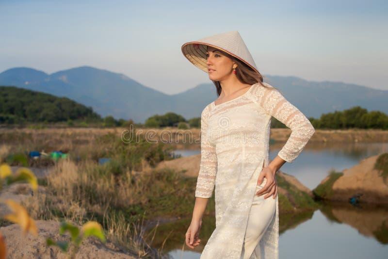 ξανθό κορίτσι στα βιετναμέζικα χαμόγελα φορεμάτων ενάντια στις λίμνες χωρών στοκ φωτογραφία με δικαίωμα ελεύθερης χρήσης