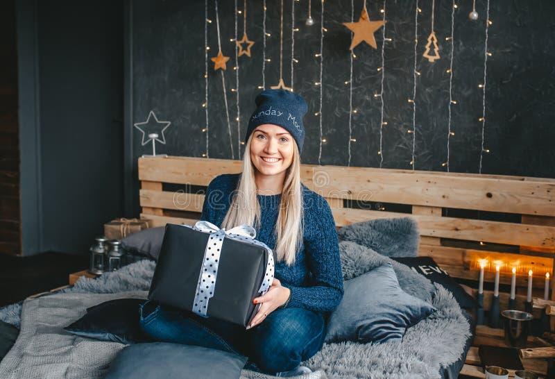 Ξανθό κορίτσι στην μπλε ΚΑΠ, που φορά τον περιστασιακούς μπλε άλτη και το τζιν παντελόνι, κρατώντας το κιβώτιο δώρων, που κάθεται στοκ εικόνες