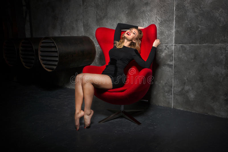Ξανθό κορίτσι στη μαύρη συνεδρίαση φορεμάτων στην κόκκινη πολυθρόνα στοκ φωτογραφίες με δικαίωμα ελεύθερης χρήσης