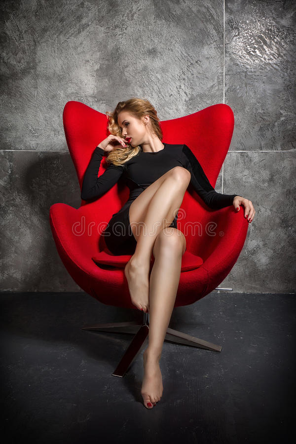 Ξανθό κορίτσι στη μαύρη συνεδρίαση φορεμάτων στην κόκκινη πολυθρόνα στοκ φωτογραφία