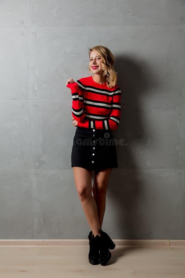 ξανθό κορίτσι στο κόκκινο ριγωτό πουλόβερ στοκ εικόνα
