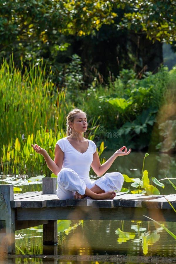 Ξανθό κορίτσι της δεκαετίας του '20 της Zen που σκέφτεται, περιβάλλον νερού στοκ φωτογραφίες