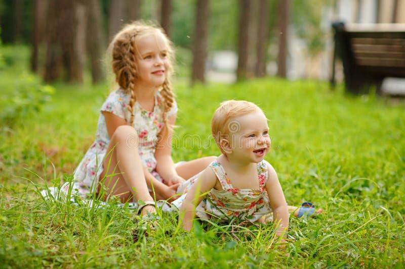 Ξανθό κορίτσι δύο γοητευτικό αδελφών που αγκαλιάζει και που γελά στο gra στοκ εικόνες