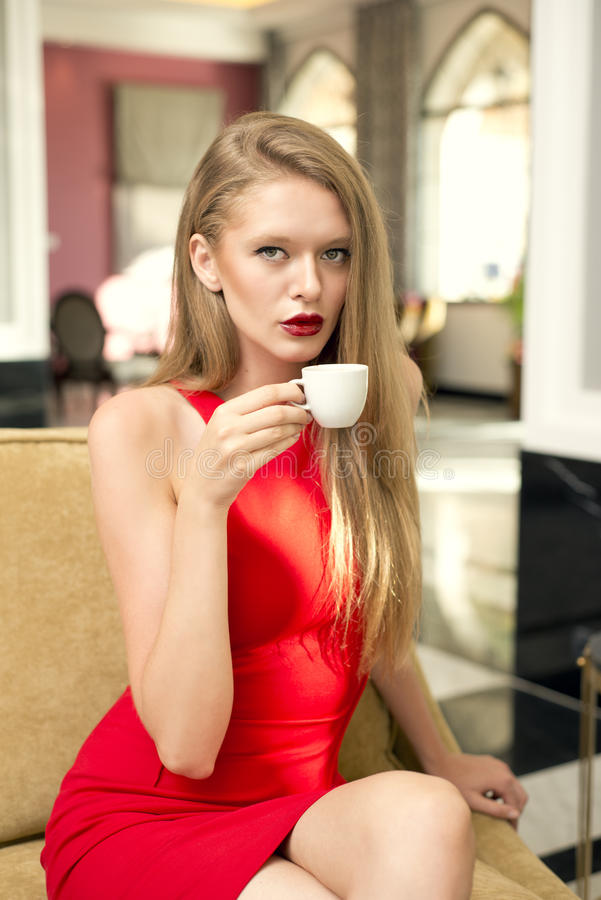 Ξανθό κορίτσι Beuatiful που έχει τον καφέ στο λόμπι στοκ φωτογραφίες