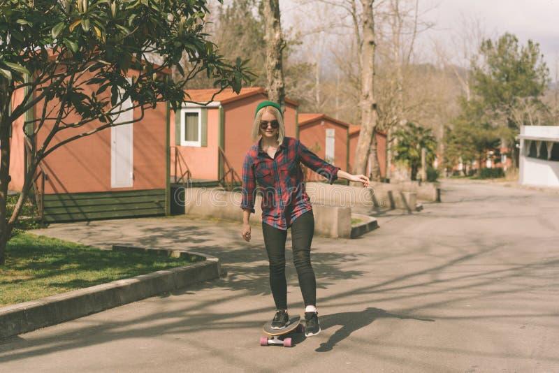 Ξανθό κορίτσι hipster που οδηγά skateboard στοκ εικόνα με δικαίωμα ελεύθερης χρήσης