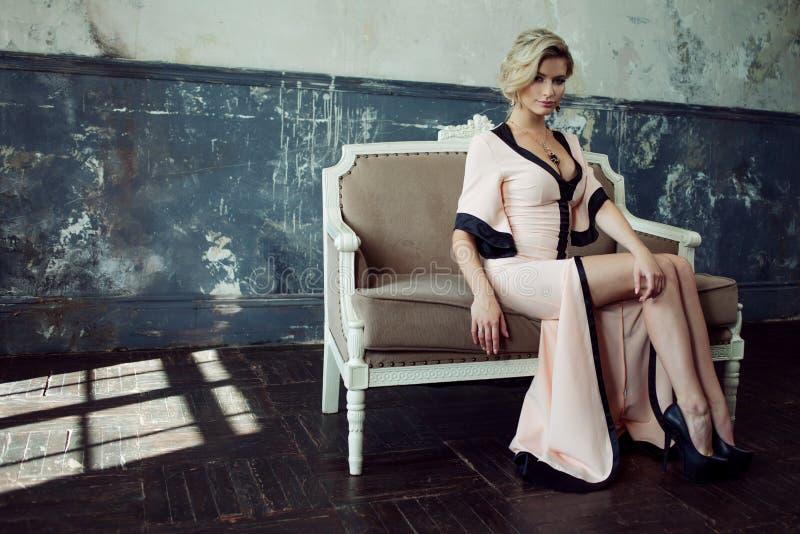 ξανθό μοντέλο τριχώματος μό&del Νέα ελκυστική γυναίκα, που εγκαθιστά στον καναπέ, εκλεκτής ποιότητας ύφος στοκ εικόνες