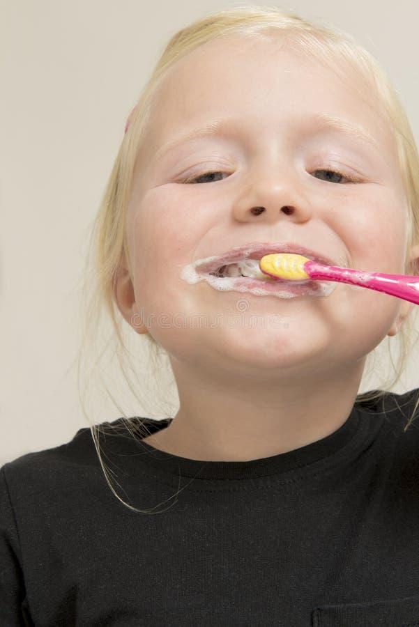 Ξανθό παιδί που βουρτσίζει τα δόντια της με μια ρόδινη οδοντόβουρτσα στοκ φωτογραφία