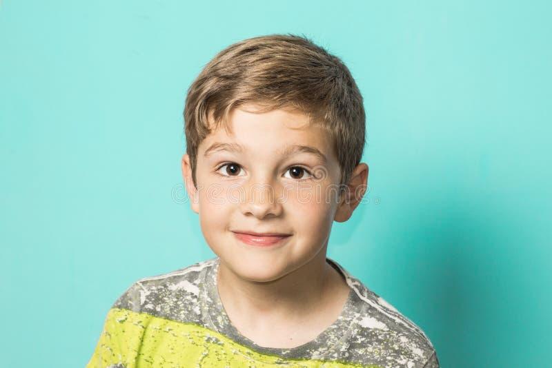 Ξανθό παιδί που εξετάζει τη κάμερα και το χαμόγελο Παιδί με την έκφραση στο ευτυχές πρόσωπο στοκ εικόνα