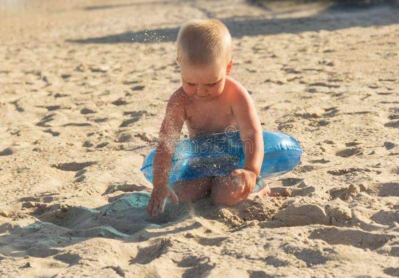 Ξανθό παιχνίδι αγοριών με την άμμο στην ηλιόλουστη καυτή παραλία στοκ εικόνα