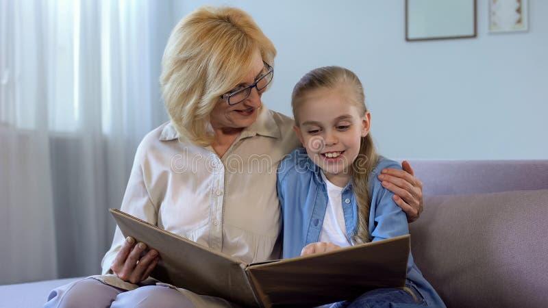 Ξανθό παραμύθι ανάγνωσης grandkid με τη γιαγιά της στο σπίτι, ενότητα στοκ φωτογραφία
