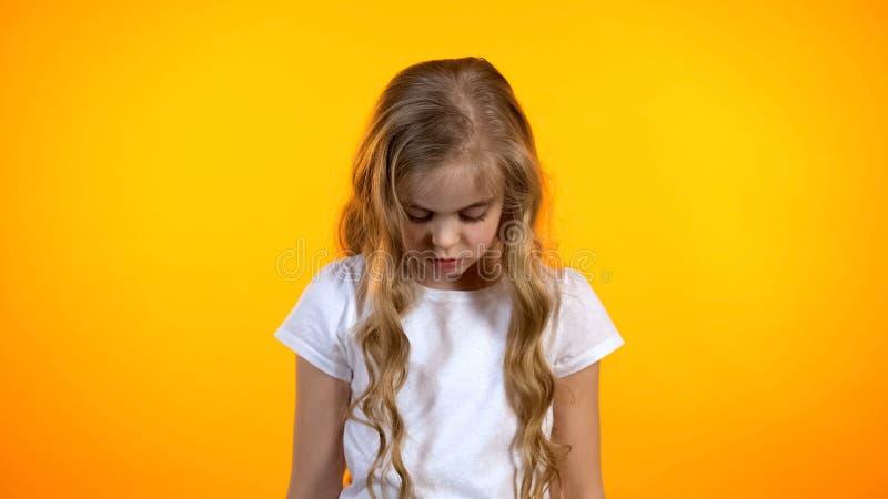 Ξανθό σγουρό κορίτσι που κοιτάζει κάτω από απομονωμένος στο πορτοκαλί υπόβαθρο, που αισθάνεται ένοχο στοκ εικόνα