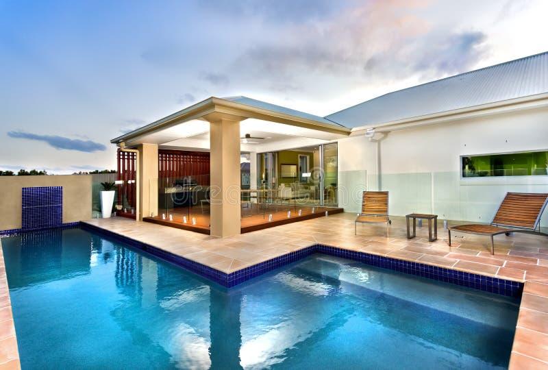 Ξενοδοχείο πολυτελείας με την μπλε πισίνα νερού στο σκοτεινό ουρανό στοκ εικόνα