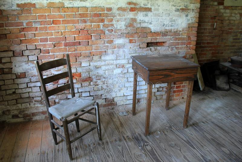 Ξεπερασμένος Ole τουβλότοιχος στην ερείπωση, με τον ξύλινους πίνακα και την καρέκλα στοκ εικόνες
