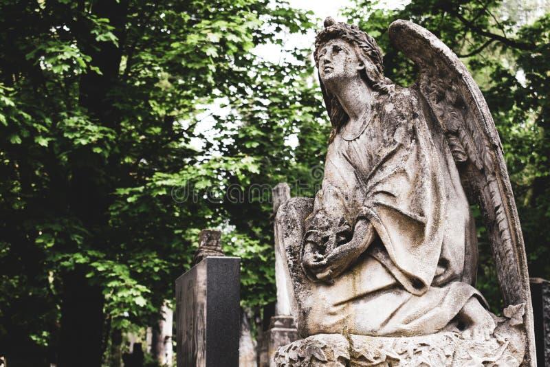 Ξεπερασμένο παλαιό ανάστημα του αγγέλου με το σταυρό στον ενταφιασμό στο νεκροταφείο στο νεκροταφείο Lychakiv, Lviv στοκ φωτογραφίες με δικαίωμα ελεύθερης χρήσης
