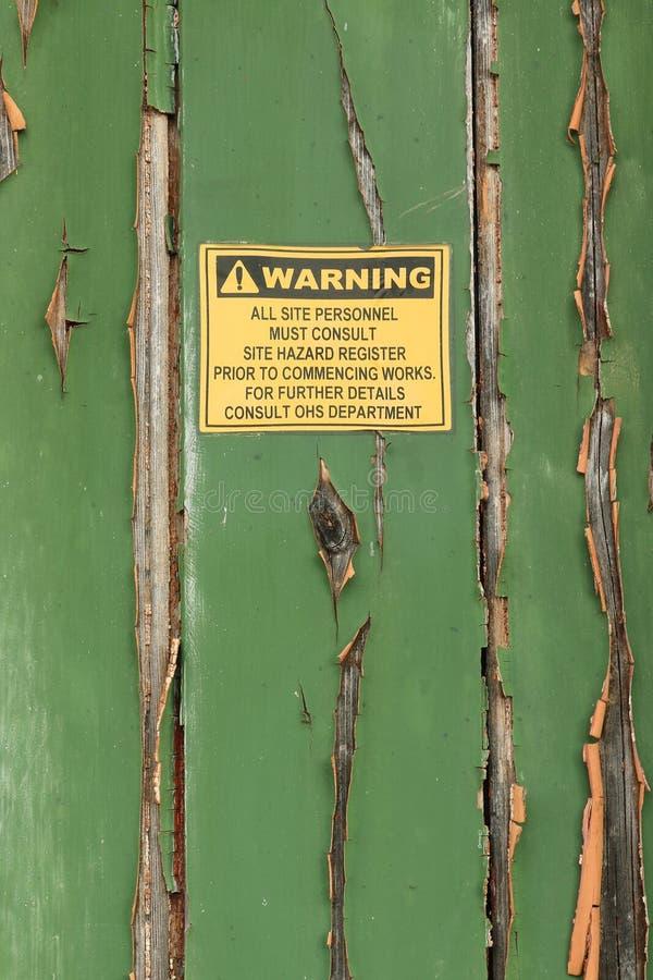 Ξεπερασμένο προειδοποιητικό σημάδι να ξεφλουδίσει, ξεφλουδίζοντας χρωματισμένη ξύλινη πόρτα στοκ φωτογραφίες