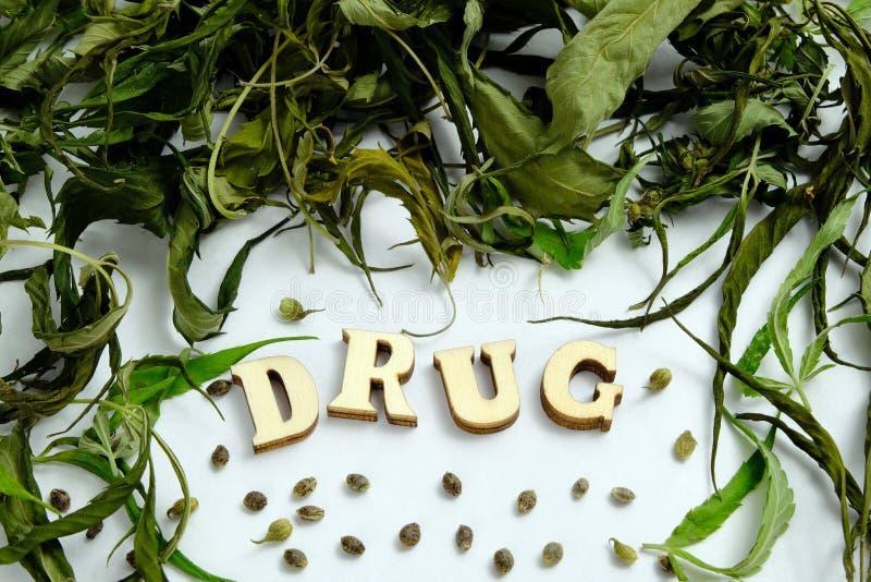 Ξεράνετε τα φύλλα και τα σιτάρια της μαριχουάνα υπό μορφή πλαισίου Το ΦΑΡΜΑΚΟ λέξης αποτελείται από τις ξύλινες επιστολές στοκ εικόνες με δικαίωμα ελεύθερης χρήσης
