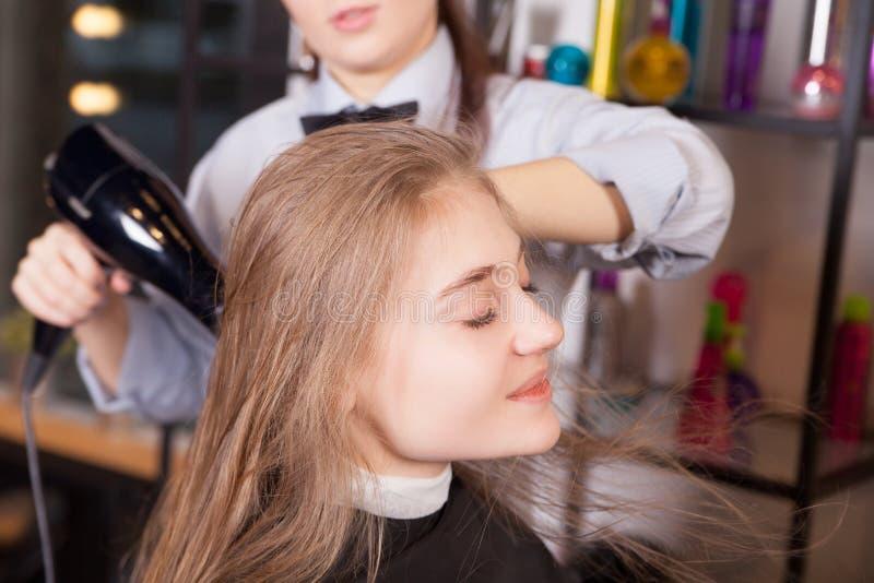 Ξεραίνοντας τρίχα Hairstylist ξανθή στο σαλόνι στοκ εικόνες