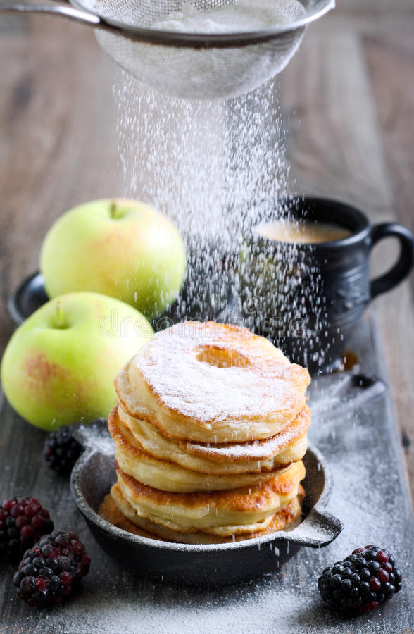 Ξεσκόνισμα με τη ζάχαρη τήξης πέρα από fritters μήλων στοκ εικόνες