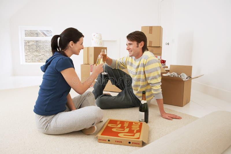 Ξετυλίγοντας τάπητας ζεύγους στο νέο σπίτι στοκ φωτογραφίες