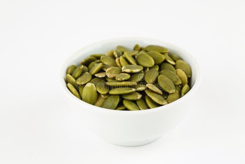 Ξεφλουδισμένοι πράσινοι σπόροι κολοκύθας σε ένα άσπρο κύπελλο στοκ εικόνα με δικαίωμα ελεύθερης χρήσης