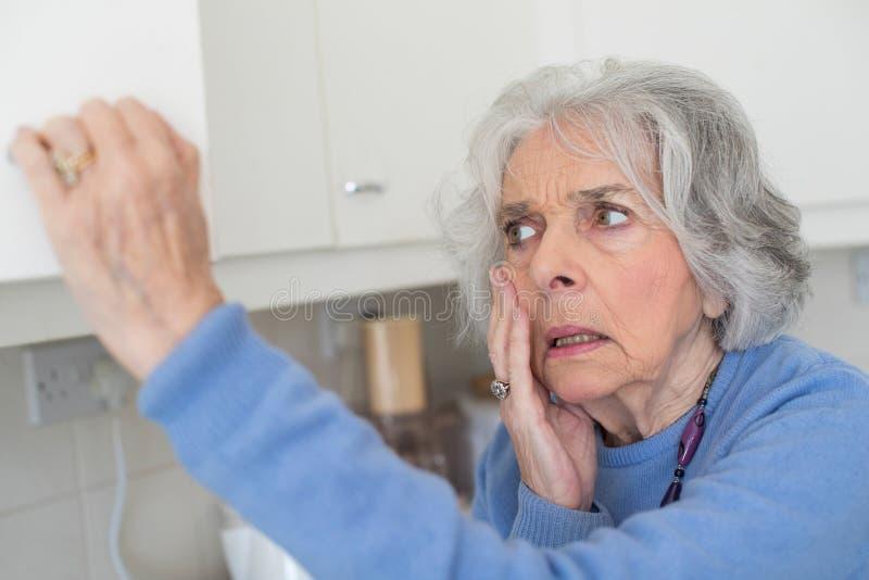 Ξεχασιάρης ανώτερη γυναίκα με την άνοια που κοιτάζει στο ντουλάπι στοκ φωτογραφία