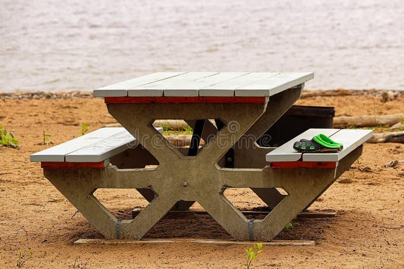 Ξεχασμένα παπούτσια σε έναν πίνακα πικ-νίκ στην παραλία στοκ εικόνα