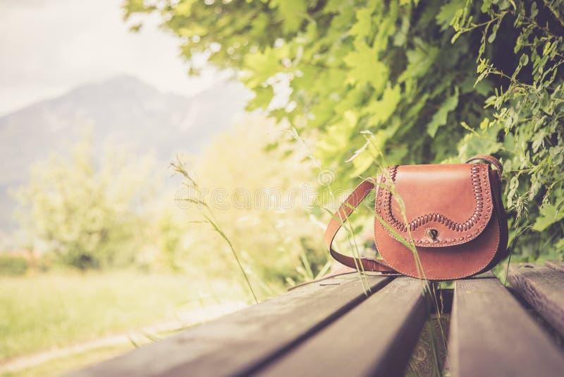 Ξεχασμένη τσάντα δέρματος σε έναν πάγκο πάρκων, κανένας στοκ φωτογραφίες
